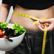 ウエストを測定しているダイエット中の男性とサラダ
