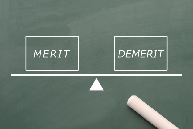 メリットとデメリットを英単語でかきシーソーにのせ比較している